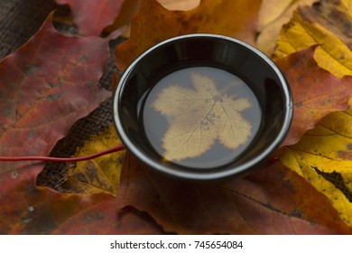 Autumn tea ceremony still life black cup of tea closup background