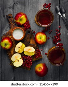 Autumn tea drink (compote) from apples and berries of Kalina. Ingredients are sugar, calyx berries, fresh sliced apples. Rustic gray vintage background. Top view