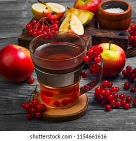 Autumn tea drink (compote) from apples and berries of Kalina. Ingredients are sugar, calyx berries, fresh sliced apples. Rustic gray vintage background.