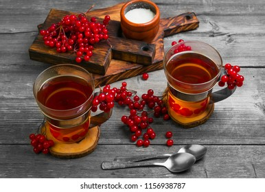 Autumn tea drink (compote) from berries of Kalina. Ingredients are sugar, calyx berries. Rustic gray vintage background.