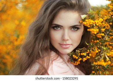 Autumn teen Girl Portrait. Beautiful young Woman over yellow leaves in the autumn park. Outdoor photo.
