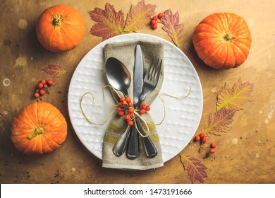 Autumn and Thanksgiving day table setting with leaves, pumpkins, empty white plate and vintage cutlery on brown stone table. Flat lay. Top view.