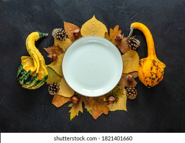 Autumn and Thanksgiving day table setting with fallen leaves, decorative pumpkins, the empty white plate on the dark background