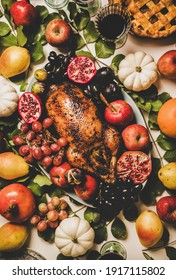 Autumn Thanksgiving, Friendsgiving, family party gathering celebration dinner. Flat-lay of Fall decorated table with roasted duck in seasonal fruits and vegetables, apple pie and drinks in glasses