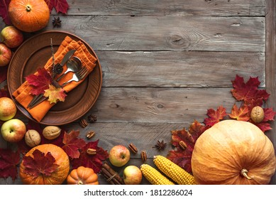 Autumn Thanksgiving Table Setting. Plate and cutlery on wooden table with pumpkins and autumn decor, Thanksgiving holiday menu concept.