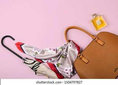 Autumn theme flat lay of female leather handbag and other accessories on pastel pink background