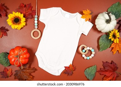 Autumn theme white baby romper onesie jumpsuit mockup flatlay on brown tan background with autumn leaves and punpkins. Product mock up with negative copy space.