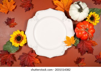 Autumn theme white dinner plate mockup flatlay on brown tan background with autumn leaves and punpkins. Product mock up with negative copy space.