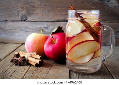 Autumn themed detox water with apple, cinnamon and red pear in a mason jar on a rustic wood background