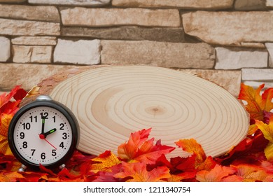 Autumn Time Background, Some fall leaves with cut wood plaque and an alarm clock on weathered brick with copy space for your message