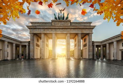 Autumn time in Berlin: the historical Brandeburger Tor (Gate) during sunset time with golden leaves at the trees
