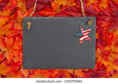 Autumn time with a chalkboard with a retro stars and strips star and fall leaves with copy space for your message