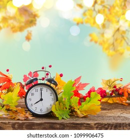 Autumn time - fall multicolored leaves with alarm clock border on fall garden background
