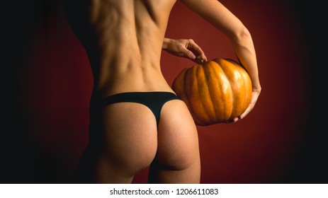 Autumn time for Fashion sale. Night Party background. Halloween poster with pumpkins. Copy space for text. The Most Popular Candy for Halloween. Woman shows a beautiful ass or butt