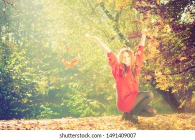 Autumn time. Fun and carefree. Cheerful lovely young woman playing with leaves. Girl relax in autumnal park forest surrounded by trees with flying leaf.