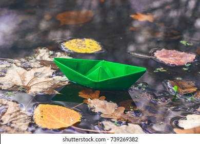 Autumn time. Paper boat floating on the stream, fallen dry leaves on the water surface. Back to school. Green, red and yellow leafs. Beautiful nature background. Goodbye autumn.