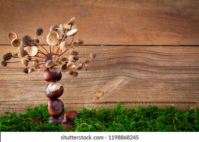 autumn tinker tinker tree made with chestnuts  and calybium of acorns  on wooden background