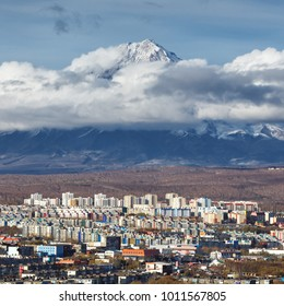 Autumn top view of cityscape of Petropavlovsk Kamchatsky City, residential buildings on background scenery active Koryak Volcano in beautiful clouds. Eurasia, Russian Far East, Kamchatka Peninsula.
