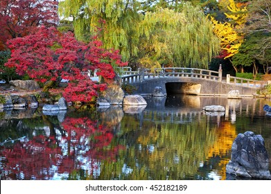Autumn traditional japanese landscape with pond and trees and stone bridge in Zurumai park, Nagoya, Japan