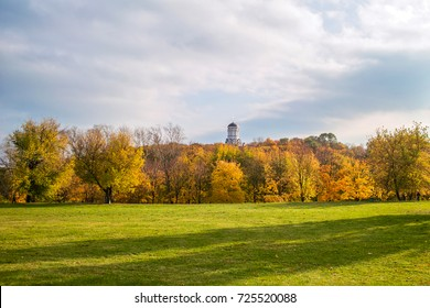 Autumn trees with a meadow and a church on the hill