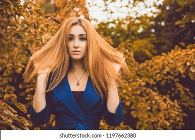 Autumn trend, stylish makeup and hair style. Woman portrait at vintage tones. Red hair lady in blue fur coat