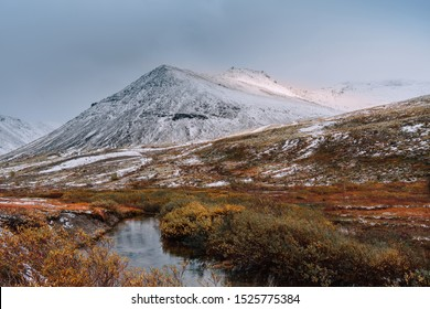 Autumn tundra and cold river on the background of  misty snow-capped mountains, Arctic, Kola Peninsula