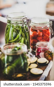 Autumn vegetable pickling and canning. Ingredients for cooking and glass jars with homemade vegetables preserves on wooden table, close-up. Healthy organic fermented food concept