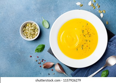 Autumn vegetable or pumpkin soup in white bowl on kitchen table top view.