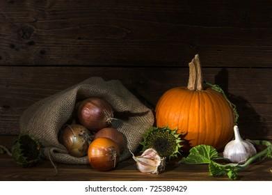 autumn vegetables on wooden table in dark