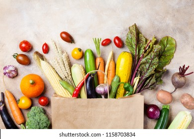 Autumn vegetables in shopping paper bag on kitchen table top view.
