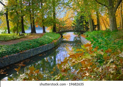 Autumn view of a bridge over a stream leading into the lake at Golden Head Park in Lyon, France.