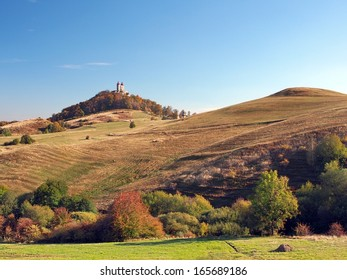 Autumn view of colorful Ostry vrch hill near Banska Stiavnica town also known as Schemnitz, Selmecbanya with late-Baroque Calvary. Banska Stiavnica is inscribed in UNESCO.