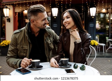 Autumn walk. Cafe. Couple. Love. Man and woman in warm casual clothes are drinking coffee, talking and smiling while sitting in the cafe outdoors