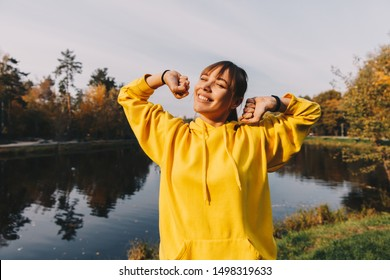 Autumn walk. Nature. Harmony. Happy girl in yellow hoodie is stretching and smiling while standing near a lake in the park