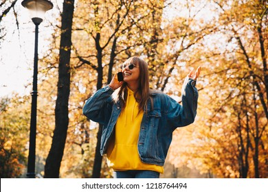 Autumn walk. Technologies. Happy girl in jean jacket and sunglasses is talking on the mobile phone and smiling while walking in the park