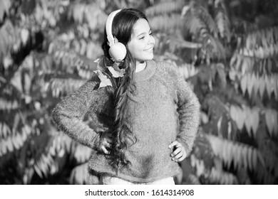 Autumn walks with nice songs. Listening audio best way help child improve vocabulary. Kid girl relaxing near autumn tree with headphones. Music for autumn mood. Listening song. Enjoy music fall day.