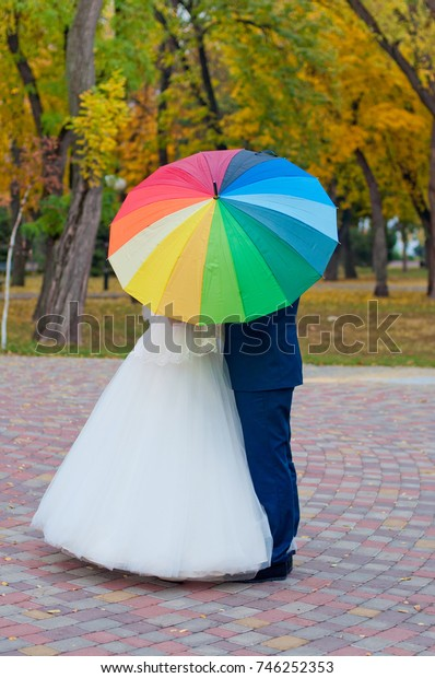 Autumn wedding. Bride and groom staying under colorful umbrella near yellow trees in park