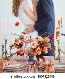 Autumn wedding concept. Bride and groom near decorated table with autumn flowers, candles and table setting