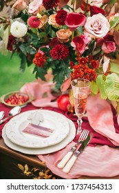 Autumn wedding table setting. Luxury stylish autumn wedding decor. Flowers and tableware on the wedding banquet. Styled romantic dinner in red color