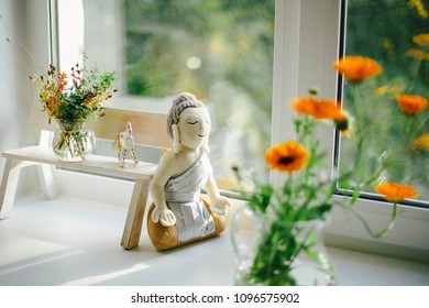 Autumn window with a buddha figure, a white wooden bench, a bouquet of flowers and spicy herbs on it and an autumn landscape outside the window