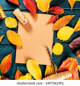 Autumn wine design template with a wine cork and corkscrew on a brown kraft paper with vibrant fall leaves forming a frame for text and logo, on a dark rustic wooden background