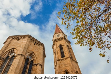 Autumn and winter in Arezzo. View of gothic cathedral apse and iconic bell tower with yellow leaves and cloudy sky
