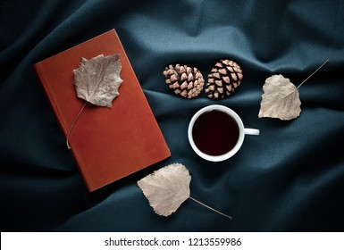 Autumn winter atmosphere. A cup of tea, dry leaves, pine cones on the dark bed sheet. Top view. Flat lay.