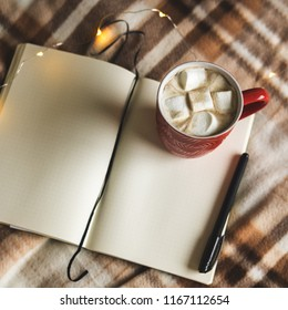 Autumn and winter background with notebook, pen, garland, mug of cocoa, coffee or hot chocolate with marshmallow on plaid. Concept of work, drawing up plans in warm cozy home environment