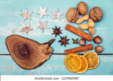 Autumn or Winter Background with spices, stars, nuts and olive wood slice on blue table