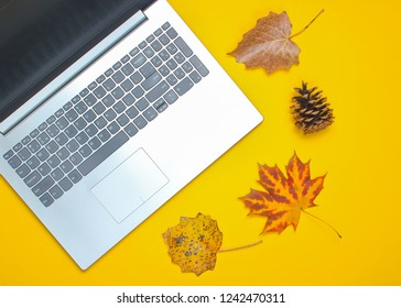 Autumn winter business still life. Laptop, fallen leaves,pine cone on a yellow background. Top view.