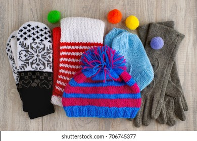 Autumn and winter clothes. Hat, gloves, mittens, scarves from the cold. Knitted clothes. Hat, scarf, socks, gloves on a wooden background. View from above. Hat, gloves, scarf and mittens folded.