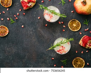 Autumn and winter cocktails idea - white sangria with rosemary, pomegrante and lemon juice and ingredients on black cement background. Copy space. Top view or flat-lay.
