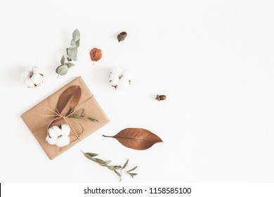 Autumn or winter composition. Gift, dried autumn leaves, cotton flowers on white background. Flat lay, top view, copy space