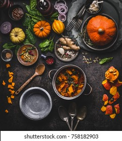 Autumn and winter cooking and eating with pumpkin dishes. Vegetarian stew in cooking pot with spoon and vegetables ingredients on dark kitchen table background, top view. Healthy seasonal food